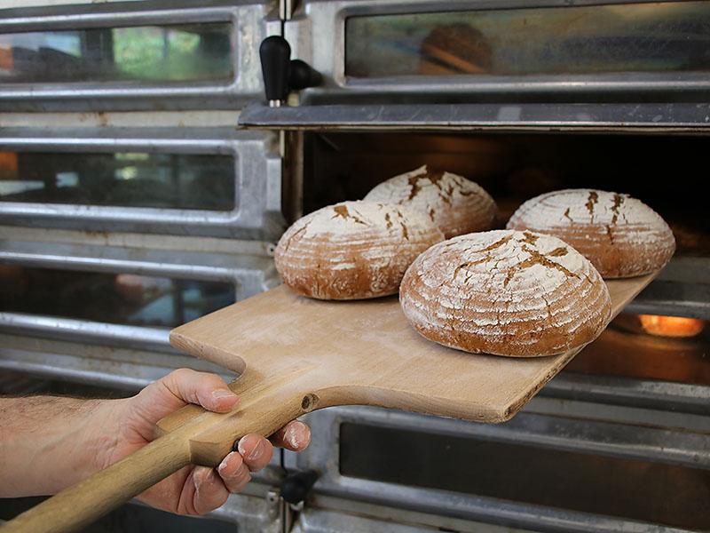 Die fertigen Brote werden mit dem Brotschieber herausgeholt