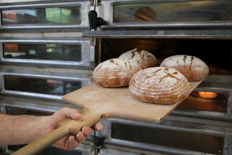 Die fertig gebackenen Brote werden aus dem Ofen entnommen